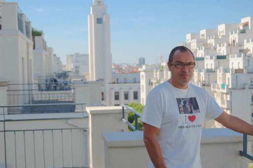 Luc Royet sur la terrasse de son appartement avec la mairie de Villeurbanne en arrière-plan. © Bertrand Enjalbal