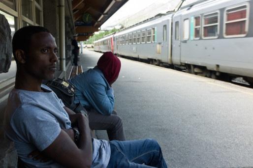 """Deux Erythréens à la gare de Modane en juin, après avoir été libérés avec une """"attestation"""" leur enjoignant de quitter le territoire français. Contrôle de la police française sur le quai de la gare de Bardonecchia en juin 2015. ©Benjamin Vanderlick"""