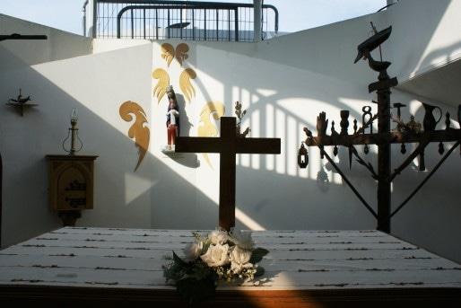 Dans la chapelle de la péniche, l'autel. A droite, la reproduction d'une croix de marinier.