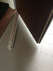 La porte d'entrée bricolée par le promoteur, parce que mal dimensionnée à la construction.