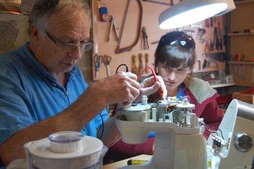 Gérard, bénévole à l'Atelier Soudé, multimètre en main cherche d'où vient la panne d'un robot mixeur. © BE / Rue89Lyon