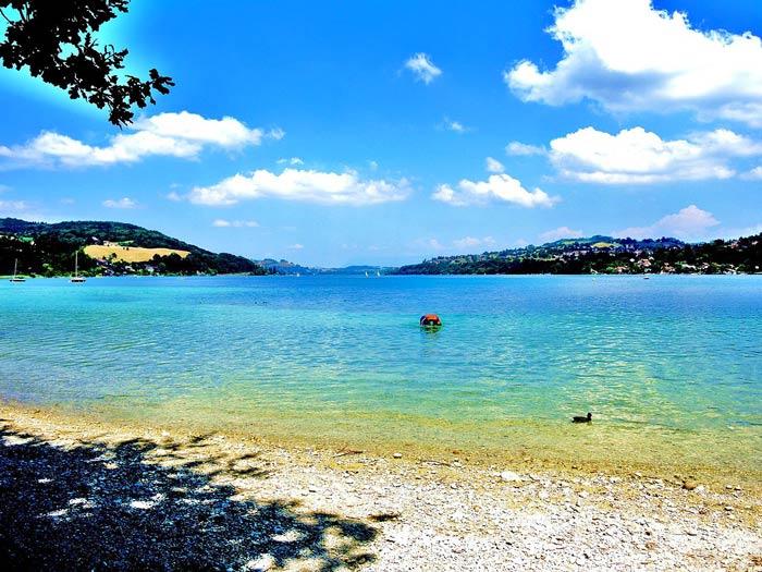L'une des plages du lac de Paladru entouré de son eau turquoise pour se baigner. CC