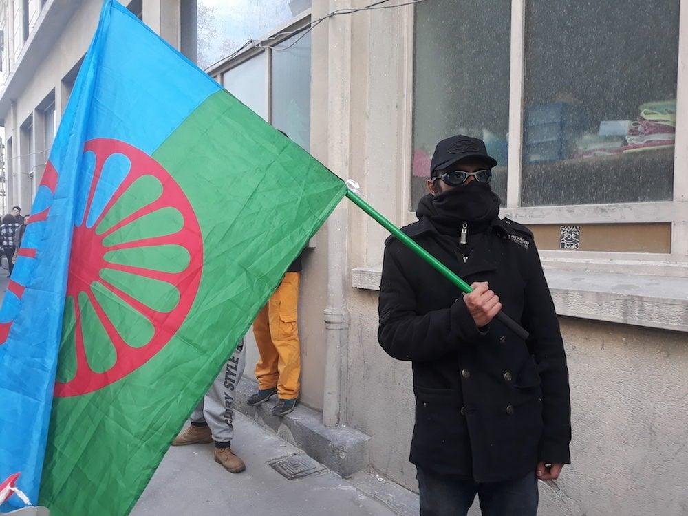 Don-Miglo, le drapeau Rom à la main, avec écharpe et lunettes de piscine pour se protéger des gaz lacrymogènes. ©LB/Rue89Lyon