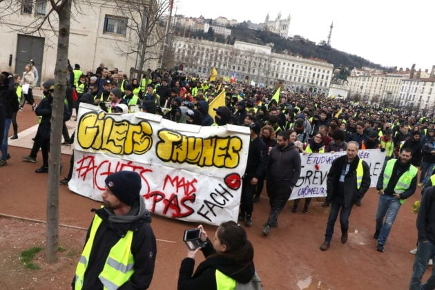"""Acte XIII, samedi 9 février 2019, départ de la manifestation des """"gilets jaunes"""" place Bellecour à Lyon. Une banderole est déployée par les antifa pour protester contre les groupuscules d'extrêmes droite. ©MG/Rue89Lyon"""