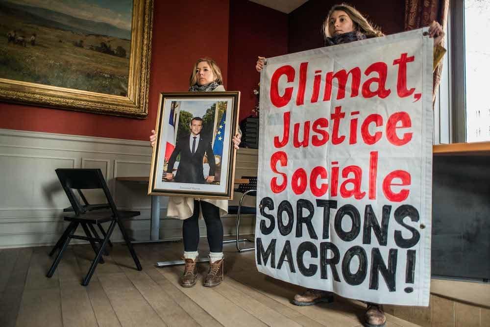 Fanny Delahalle tenant le portrait d'Emmanuel Macron dans la mairie du 2e arrondissement au moment de l'action, le 21 février dernier. ©Simon-Cavalier