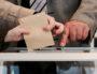 Électeur s'apprêtant à mettre son bulletin de vote dans l'urne. Photo CC par Arnaud Haegers