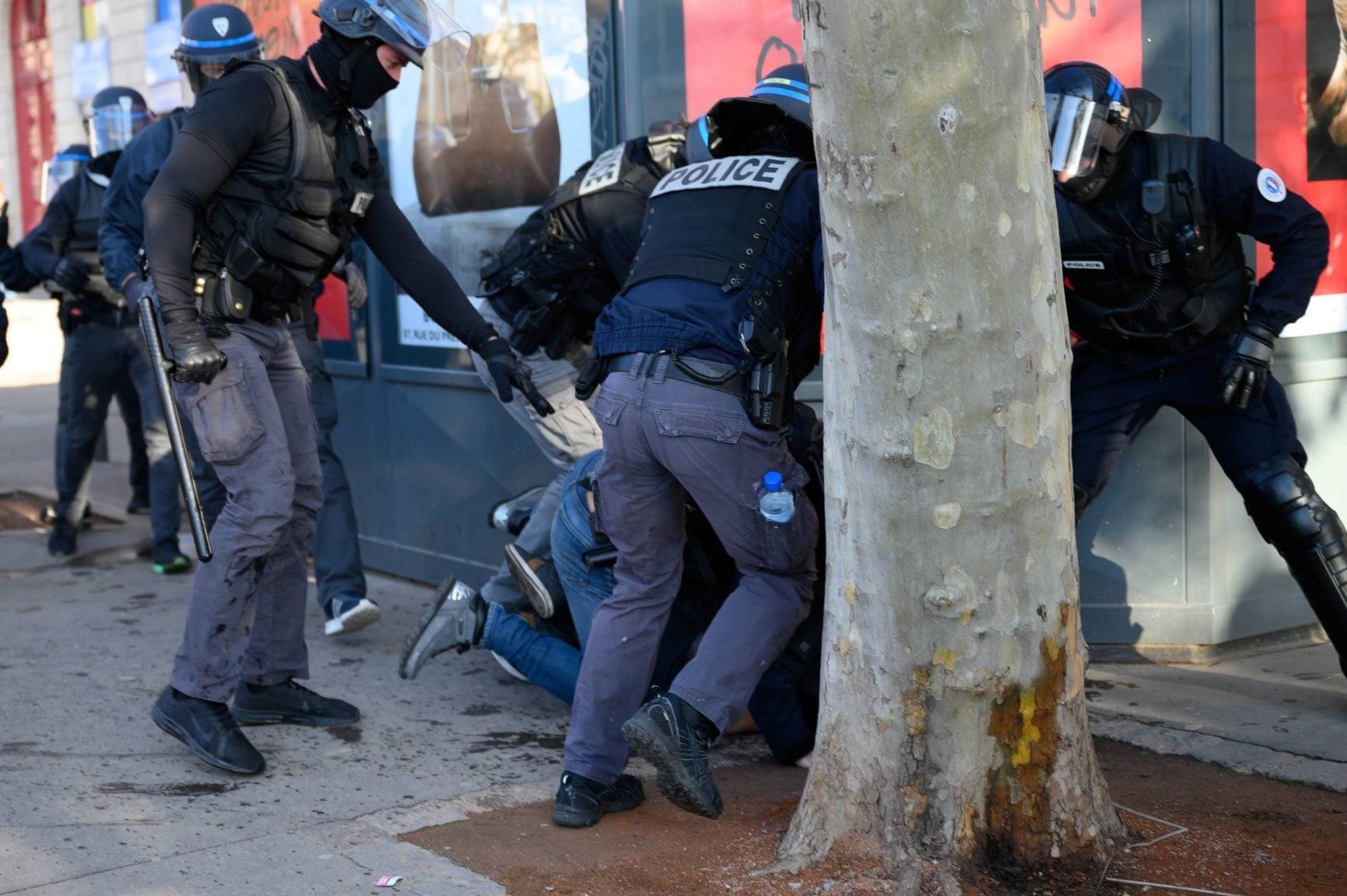 Arthur battu par des CRS entre le kiosque à journaux et un arbre de la place Bellecour. Crédit : Bastien Doudaine.