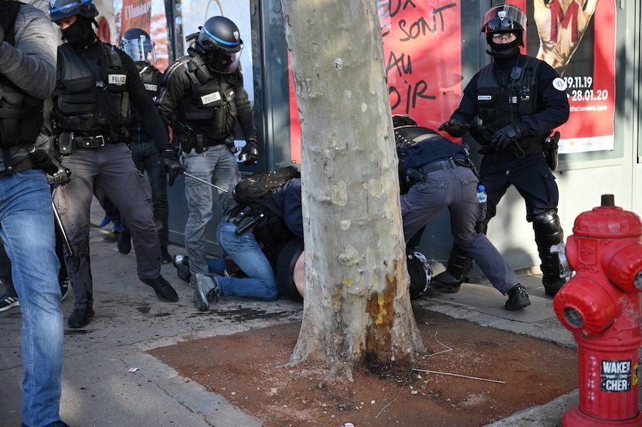 le policier qui semble être l'auteur probable du coup de matraque ; la jambe gauche de son pantalon est maculée de sang