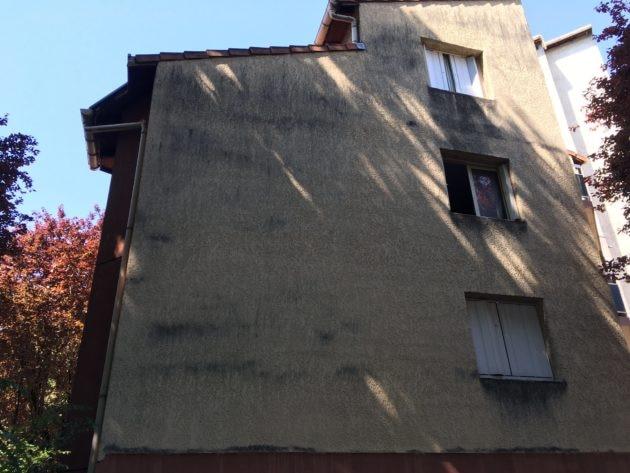 Façade d'un immeuble tachée par des traces noires